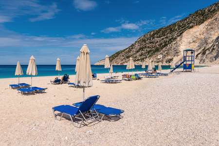 KEFALONIA, GREECE - September 30, 2017: Sun beds and parasols on beautiful Myrtos beach with white sand and water on Kefalonia island. Greece. Editorial