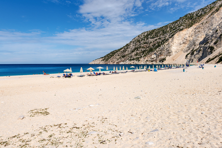 Sunbeds and parasols on beautiful Myrtos beach with white sand and blue sea water on Kefalonia island. Greece. Stock Photo