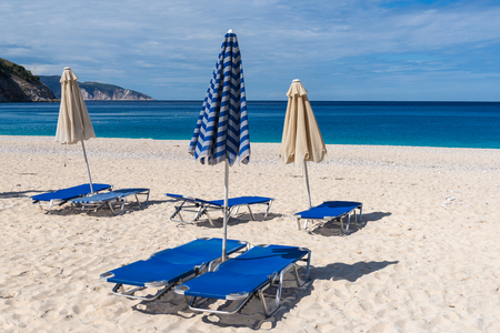 Sun beds and parasols on beautiful Myrtos beach with white sand and blue sea water on Kefalonia island. Greece.