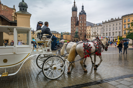 KRAKOW, POLAND - August 6, 2016: Horse carriage at main square in Krakow in rainy day. Poland. Europe. Editorial