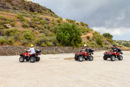 Milos, Greece, May 18, 2017: Young people driving quads on road. Quad is very popular means of transport on Milos island. Greece. Редакционное
