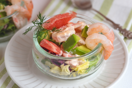 Cocktail salad with shrimp, avocado, green lettuce, grapefruit and mayonnaise sauce in a glass. Stockfoto