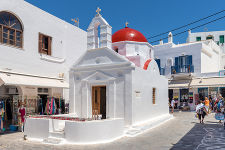 MYKONOS, GREECE - May 23, 2017: A view of typical Greek church building on square with shops in Mykonos town. Cyclades islands, Greece