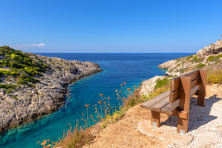 Bench on cliff with view of bay with crystal sea water. Korakonisi Island on western side of Zakynthos. Zante, Greece