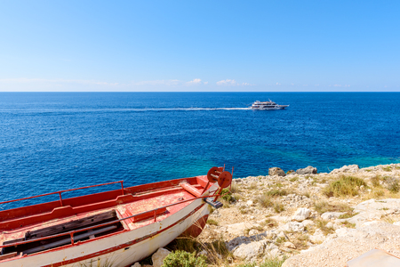 Old boat on shore and blue waters of Ionian Sea. Zakynthos island in Greece