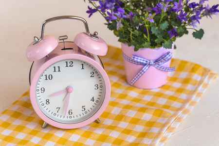Pink alarm clock and fresh flowers. Spring time change. Stock Photo