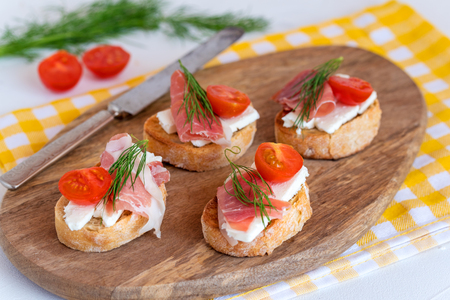 Italian prosciutto and feta cheese bruschetta decorated by tomato and dill. Antipasti on grilled baguette bread.
