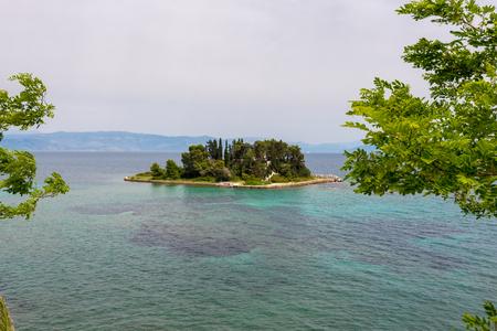 Pontikonisi, a small green island (Mouse Island) on Corfu island. Greece.