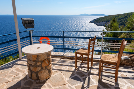 Table with chairs on terrace overlooking blue sea in summer day. Zakynthos, Greece