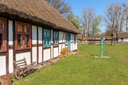 Whitewashed house with thatched roof in open-air museum in Kluki village. Poland