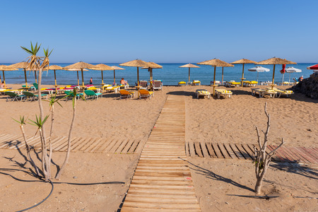 RHODES, GRECE: Wooden walkway and sun loungers with umbrellas on sandy Tsambika beach. Rhodes island, Greece