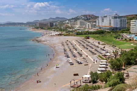 Sun loungers with umbrellas on sandy beach in Faliraki. Rhodes island, Dodecanese, Greece.