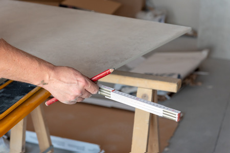 The Man Measures The Floor Tiles To Cut Them Using A Tile Cutting