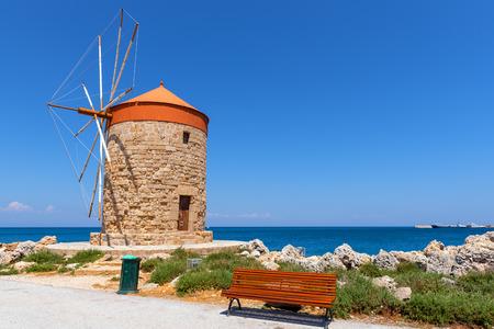 Historische windmolen op boulevard in de haven van Mandrakia. Rhodos-eiland, Griekenland Stockfoto