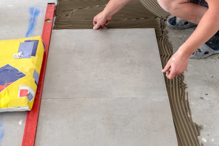 The hands of the tiler are laying the ceramic tile on the floor.