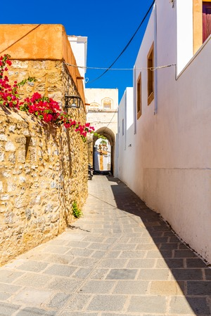 Narrow street with spring flowers on Rhodes island. Lindos village, Dodecanese, Greece. 免版税图像