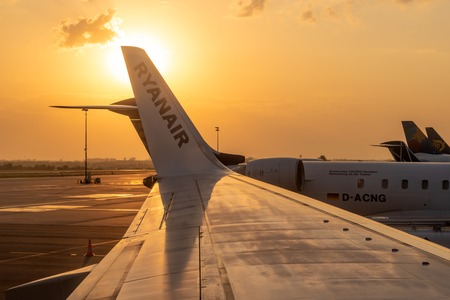 GDANSK, POLAND - September 7, 2018: View of an airplane wing with a Ryanair logo at Gdansk Lech Walesa Airport. Sunset time