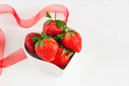 Fresh strawberries in a heart-shaped bowl for Valentine's Day.