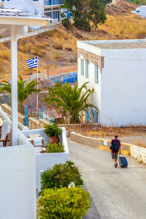 SERIFOS, GREECE - September 9, 2018: Tourist with a suitcase walking down the street on the island of Serifos.
