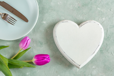 Valentines day, romantic dinner concept. Heart, tulip flower, set of dishes with cutlery. 写真素材