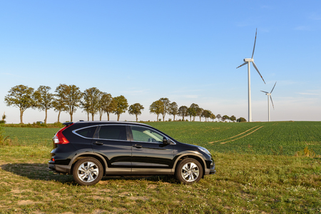 PUCK, POLAND - September 18, 2018: Honda CR-V car parked in a field on a country road next to a wind farm