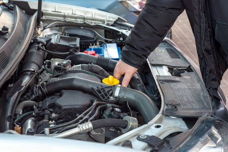 Man checking oil level in car engine.