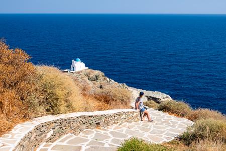 A beautiful young woman admires Eptamartyres Church in Kastro. Sifnos island, Greece