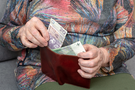 Hands of an elderly pensioner holding leather wallet with polish currency money. Concept of financial security in old age. Zdjęcie Seryjne