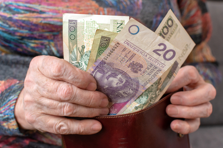 Hands of an elderly pensioner holding leather wallet with polish currency money. Concept of financial security in old age. Stock Photo