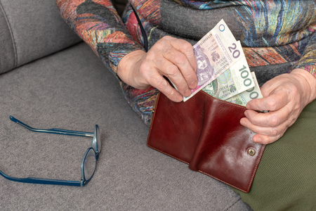 Hands of an elderly pensioner holding leather wallet with polish currency money. Concept of financial security in old age. Foto de archivo