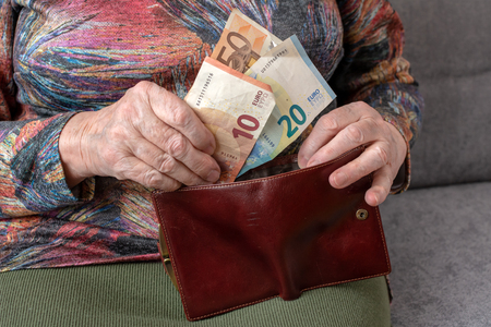 Hands of an elderly pensioner holding leather wallet with euro currency money. Concept of financial security in old age.