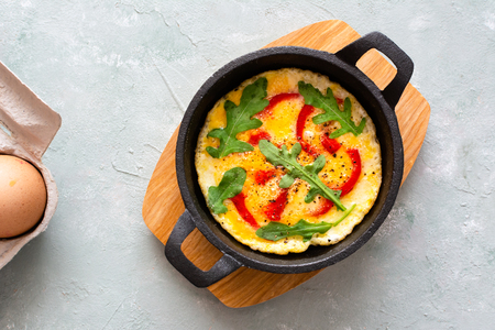 Omelette with fresh pepper and arugula. Frittata in frying pan. Stock Photo