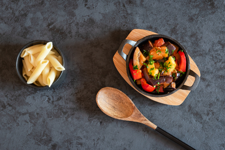 Vegetarian letcho with baked aubergine, zucchini, pepper in tomato sauce. Dish served with pasta.