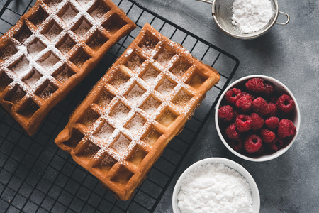 Homemade waffles with raspberries on grey table
