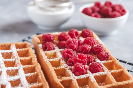 Homemade waffles with raspberries and powdered sugar