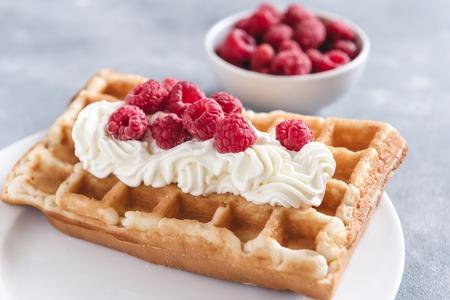 Homemade waffles with raspberries and cream Фото со стока
