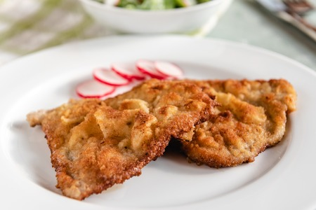 Fried pork chop in breadcrumbs served on white plate Фото со стока