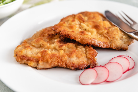 Fried pork chop in breadcrumbs served with radishes. Фото со стока