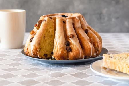 Traditional yeast ring cake with icing and raisins. Фото со стока