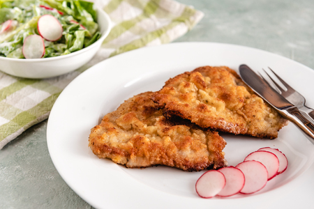 Fried pork chop in breadcrumbs served with radishes and lettuce.