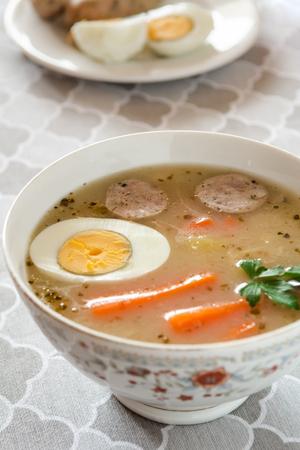 Traditional Polish soup Zurek with white sausage and egg.