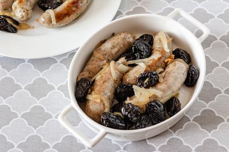 Salchicha blanca frita con cebolla y ciruelas secas.