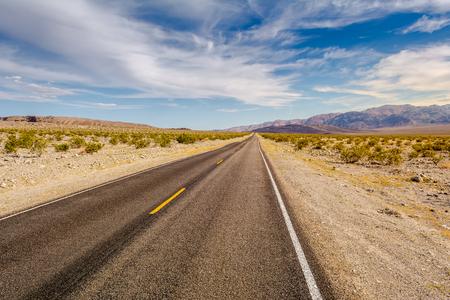 Strada attraverso un deserto e montagne in California, USA Archivio Fotografico