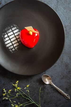 Currant cake in the shape of a red heart on a black plate.