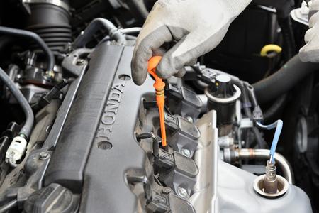 BEDZIN, POLAND - July 15, 2019: Man checking oil level in Honda CR-V car engine.