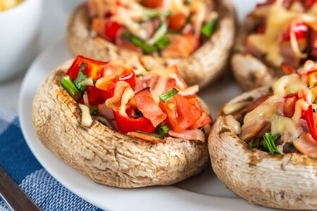 Mushrooms stuffed with bacon, tomato, red pepper, chives and cheese.