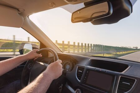 Man holding car steering wheel. Concept of safe driving.