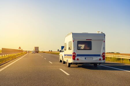 Car with recreational vehicle motor home trailer on highway. Family vacation trip concept. Stockfoto