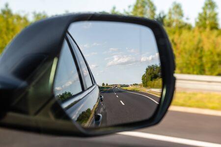 Asphalt road reflected in car mirror. Concept of safe driving.