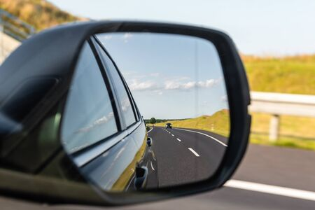 Asphalt road with vehicle reflected in car mirror. Concept of safe driving.